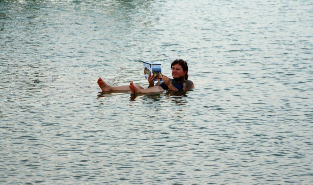 Floating and reading a book on the surface of the Dead Sea